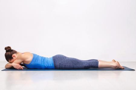 Womand relax in Hatha yoga asana Makarasana