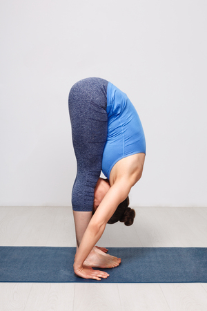 Woman doing yoga asana Uttanasana - standing forward bend 版權商用圖片