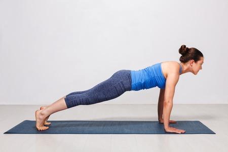 Woman doing yoga Surya Namaskar Sun Salutation asana Utthita cha Imagens