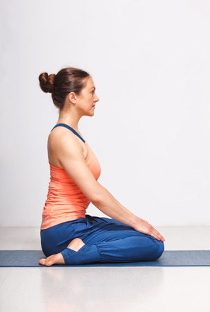 Woman in Hatha yoga asana Vajrasana