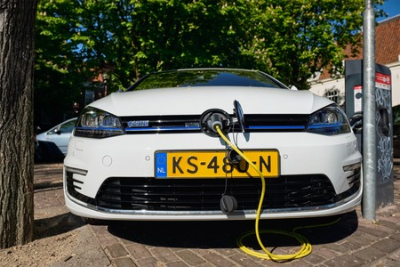 Volkswagen Golf GTE petrol-electric hybrid car being charged in the street