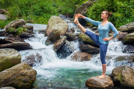hasta: Woman doing Ashtanga Vinyasa Yoga asana outdoors at waterfall