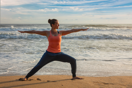 Woman doing yoga asana Virabhadrasana 1 Warrior Pose on beach on Stock Photo
