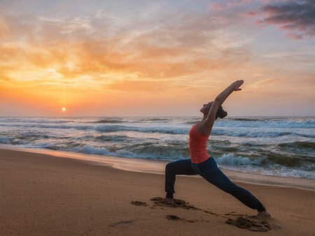 Woman doing yoga asana Virabhadrasana 1 Warrior Pose on beach on Stock Photo
