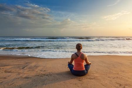 Woman doing yoga oudoors at beach - Padmasana lotus pose Stock Photo
