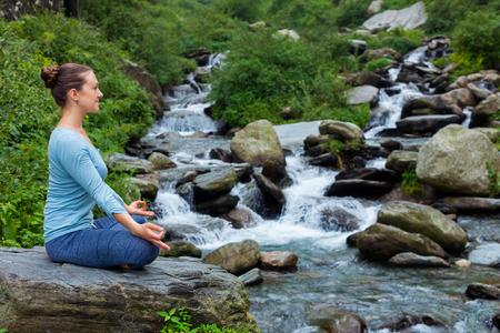 Woman in Padmasana outdoors Stock Photo