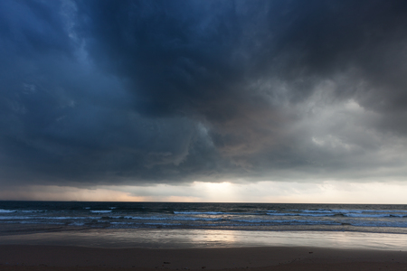 Gathering storm on beach with dark clouds. Baga, Goa, India Stock Photo