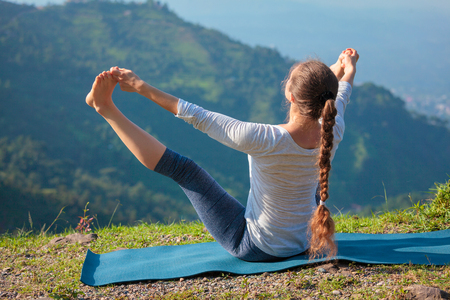 Woman doing Yoga outdoors in mountains