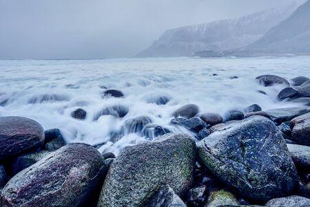 Waves of Norwegian sea surging on stone rocks. Long exposure