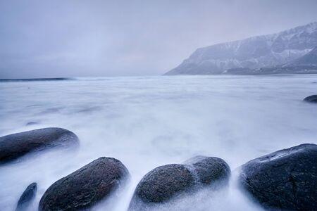 Waves of Norwegian sea surging on stone rocks. Long exposure 스톡 콘텐츠