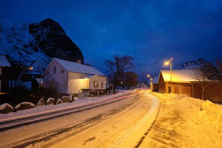 Road in Ramberg village with red traditional rorbue houses in the night, Norway