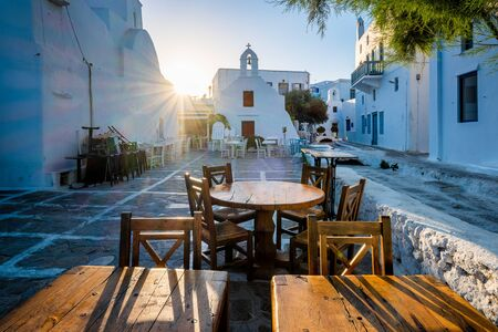 Cafe table in picturesque streets of Mykonos Chora town in famous tourist Mykonos island, Greece