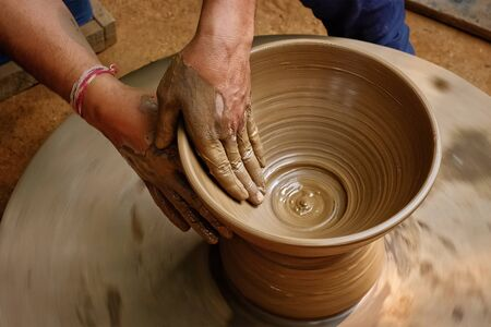 Pottery - skilled wet hands of potter shaping the clay on potter wheel. Pot, vase throwing. Manufacturing traditional handicraft Indian bowl, jar, pot, jug. Shilpagram, Udaipur, Rajasthan, India