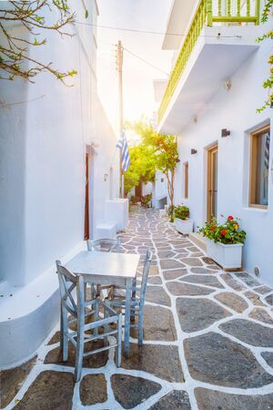 Picturesque narrow street with traditional whitewashed houses with cafe tables of Naousa town in famous tourist attraction Paros island, Greece