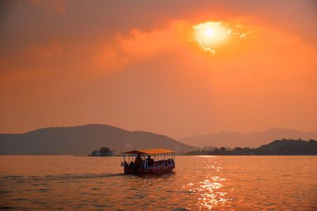 Boat in lake Pichola on sunset. Udaipur, Rajasthan, India Standard-Bild