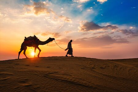 Indian cameleer camel driver with camel silhouettes in dunes on sunset. Jaisalmer, Rajasthan, India Reklamní fotografie