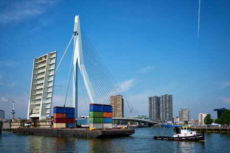 Tug boat towing barge with containers under open bascule part of Erasmusbrug bridge in Nieuwe Maas river. Rotterdam, Netherlands