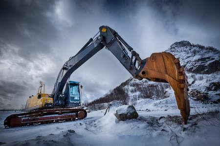 Old excavator in winter landscape