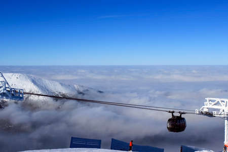 ski lift: Ski lift climb up above the clouds clear day Stock Photo