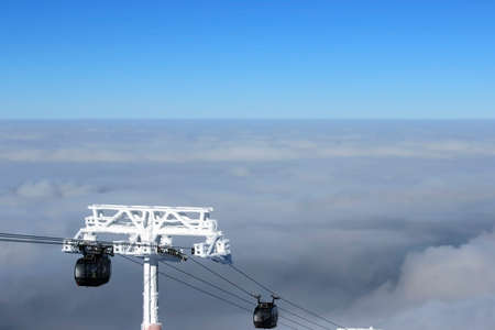 descend: Ski lift climb up above the clouds clear day Stock Photo