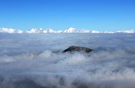 montañas nevadas: Montañas nevadas cubiertas de nubes día claro Foto de archivo