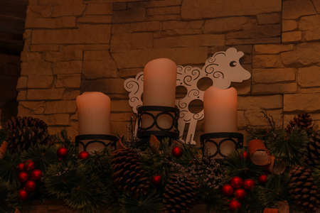 mantelpiece: Three candles with Christmas ornaments on the mantelpiece