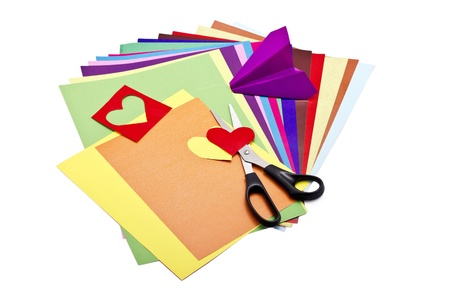 paper craft: Color paper sheets with scissors and paper craft isolated on white