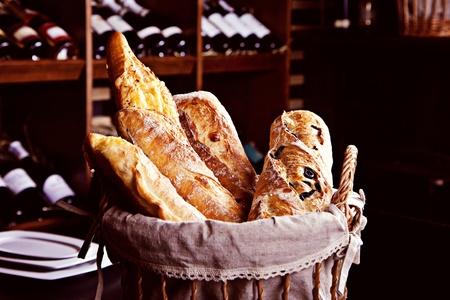 canasta de pan: Pan fresco en la cesta de camas de botellas de vino en el fondo
