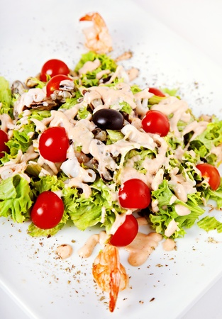 Salad with shrimp, tomatos and sauce on white plate Stock Photo