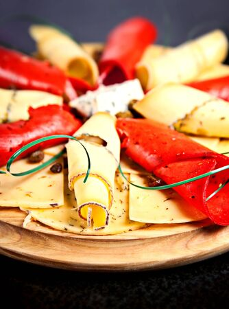 Closeup of plate with different slices of cheese on black background Stock Photo
