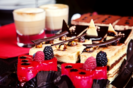 Group of different mini cakes with capuccino on background