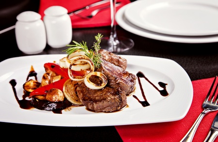 Fried beef mignon with vegetables and soy sauce served on white plate in restaurant