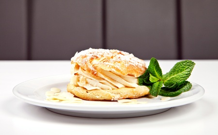 Pastry with sugar powder, almonds and mint on white background