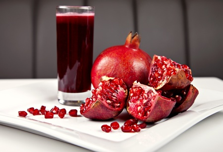 Pomegranate and juice on white plate photo