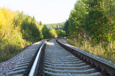 end of the line: Railroad line is going through the forest and end with a turn. Shot is made in sunny summer day. Stock Photo