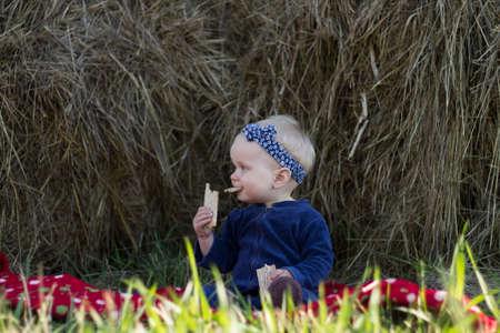 comiendo pan: El pequeño bebé está sentado junto al pajar y comer un pan crujiente.