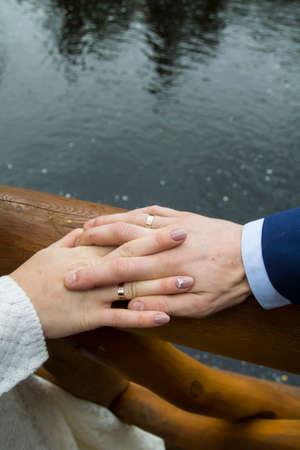 manos unidas: Primer disparo de manos unidas de pareja de recién casados. El agua corriente es en el fondo.