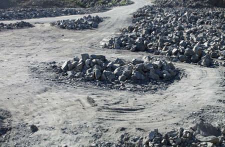 unsurfaced road: Unsurfaced road makes a sweep around the pile of stones. Stock Photo