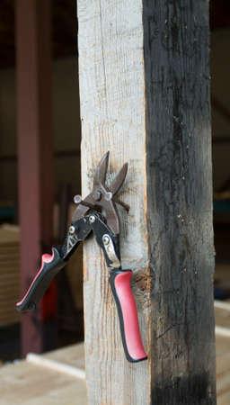 snips: Closeup shot of a tin snips hanged on nail