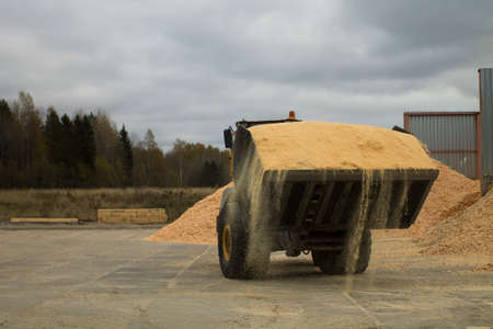 barely: Auto loader is barely seen from its scoop full with sawdust.