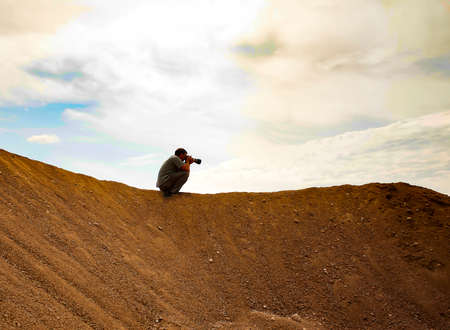 hunker: Man with photocamera is sitting at the top of sand pile and taking shots.