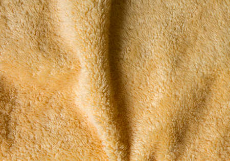 terrycloth: Texture of yellow terrycloth with vertical fold in the middle.