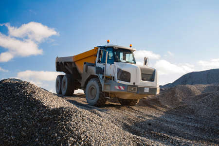 gravel pit: Dump truck working on gravel pit is driving down the hill of gravel in sunny day.