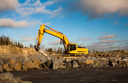 gravel pit: Yellow excavator with hydraulic hammer is working in gravel pit in sunny day. Stock Photo