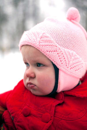 petite fille triste: Portrait of pouting baby girl made in winter day.