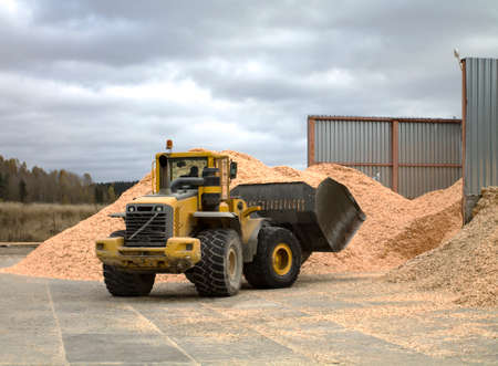 front end loader: Front end loader is working by the pile of sawdust.