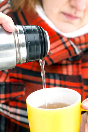 thermos: Closeup shot of a yellow cup in woman hand. She is pouring hit tea from the thermos bottle to it.