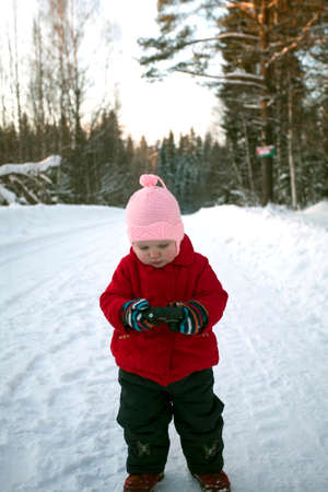 photocamera: Little girl is watching photos on the screen of digital photocamera during the walk in winter day.