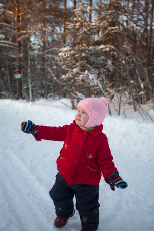 warm clothes: Little baby girl in warm clothes is dancing during the walk in winter day. Stock Photo