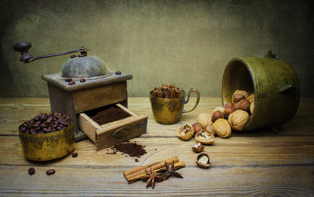 estrella de la vida: Still life with vintage coffee grinder,coffee beans,nuts,star anise and cinnamon on wooden table